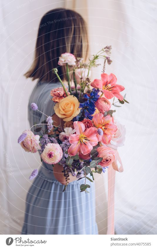 Young woman in a light blue dress holding a bouquet of flowers. Romantic concept. girl soft light beautiful vintage wedding white young beauty happy pink cute
