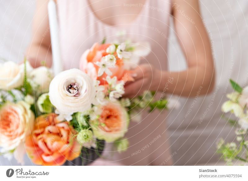 Woman hands touching a bouquet of flowers. table woman young caucasian hold holding dress white vase candles soft light decoration close up background interior
