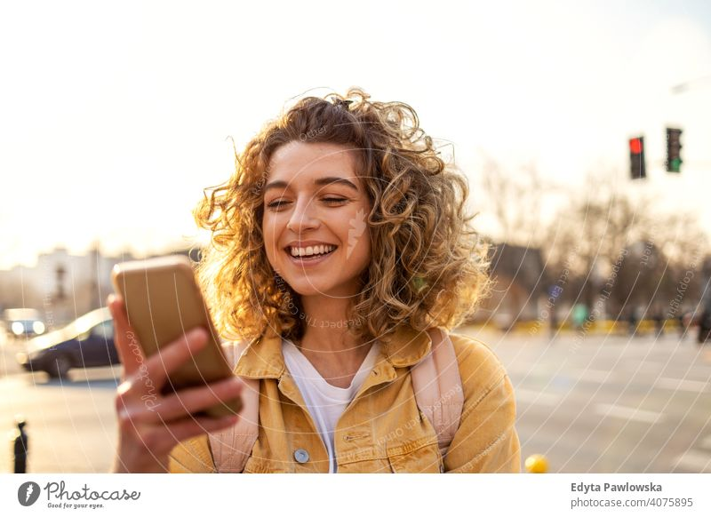 Beautiful young woman with curly hair smiling and using smartphone natural sunlight urban city hipster stylish positive sunny cool afro joy healthy freedom