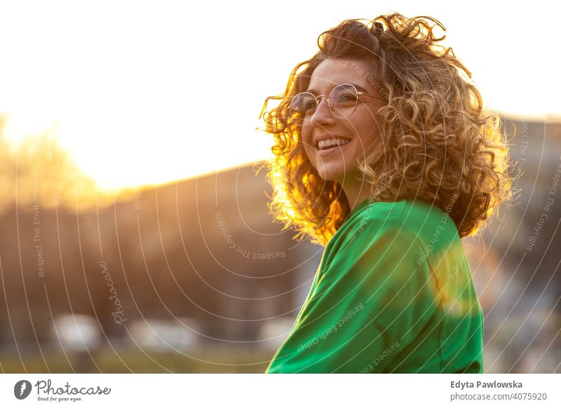 Portrait of a young woman with curly hair in the city naturally Sunlight Curly urban City Hipster stylish Positive sunny Cool Afro Joy Healthy Freedom Sunset