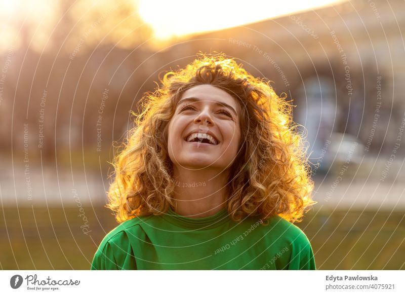 Portrait of young woman with curly hair in the city natural sunlight urban hipster stylish positive sunny cool afro joy healthy freedom sunset enjoyment summer