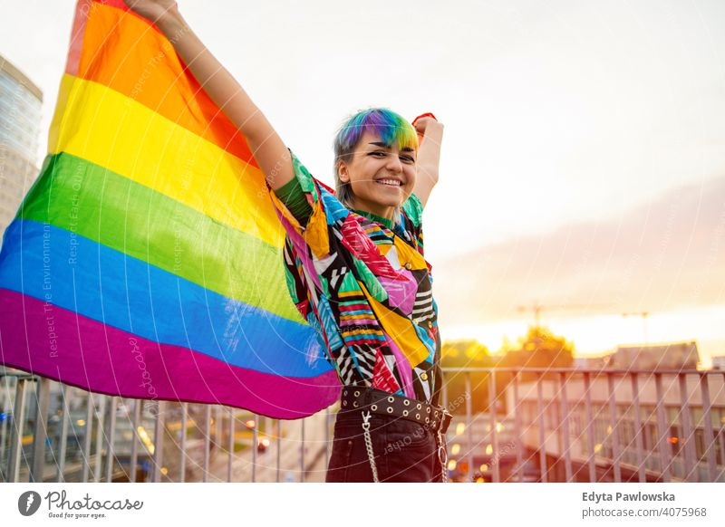 Portrait of happy non-binary person waving rainbow flag gender fluid gender fluidity lgbt equality homosexual lesbian pride gay parade man make-up identity
