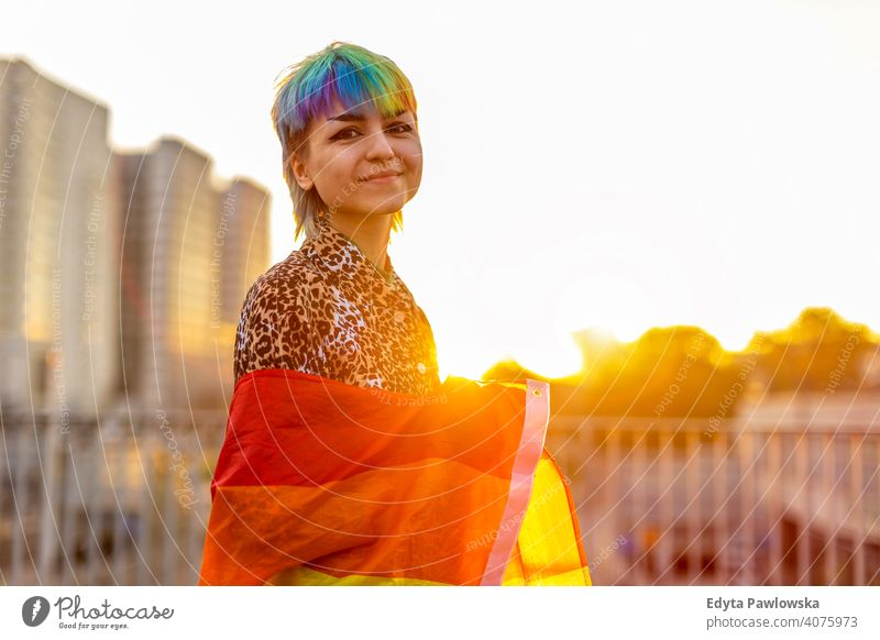 Portrait of a gender fluid person wearing rainbow flag non-binary gender fluidity lgbt equality homosexual lesbian pride gay parade man make-up identity