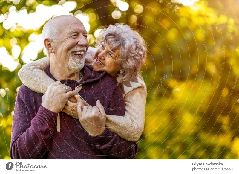 Happy senior couple enjoying a day outdoors in autumn love real people retired pensioner retirement aged grandmother grandparent grandfather two togetherness