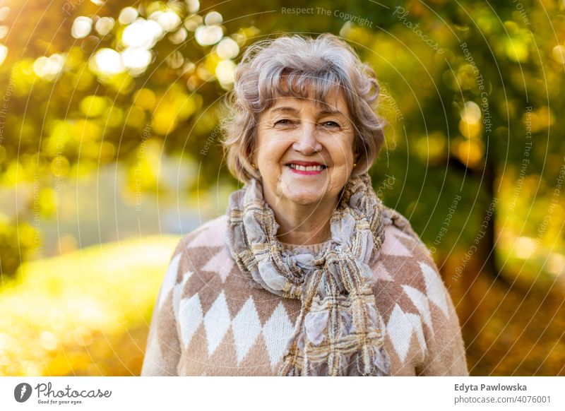 Portrait of a happy senior woman outdoors in autumn real people retired pensioner retirement aged grandmother grandparent day portrait caucasian old female