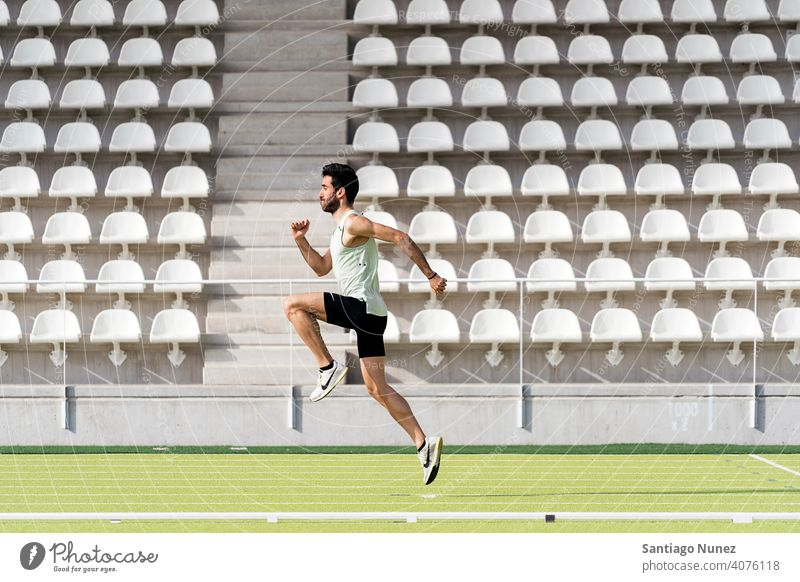 Athlete Practicing in Athletic Track side view jumping running caucasian one person sports track strength athlete runner action stadium track and field exercise