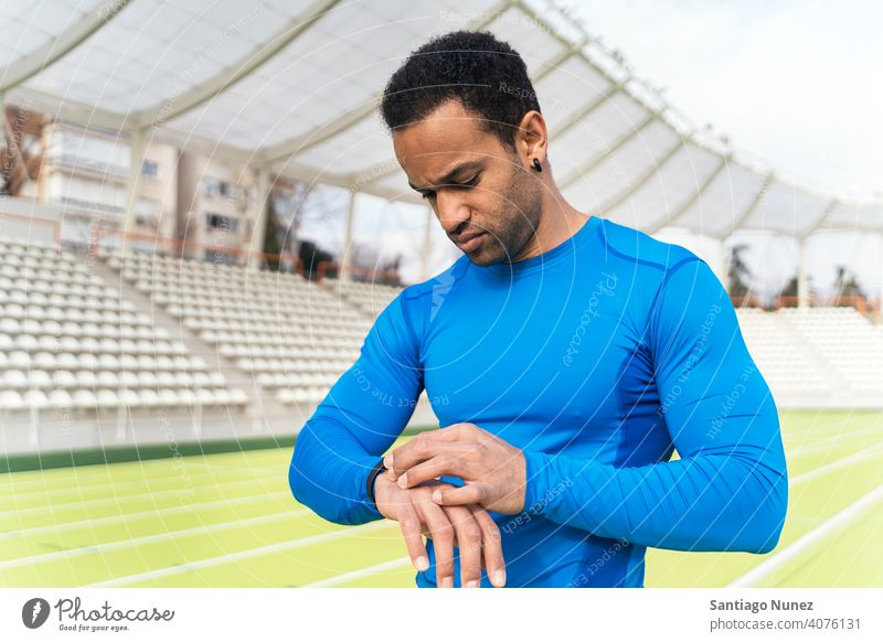 Black Athlete Using Watch portrait looking black man african american using track and field one person watch athletic athlete runner hands looking down activity