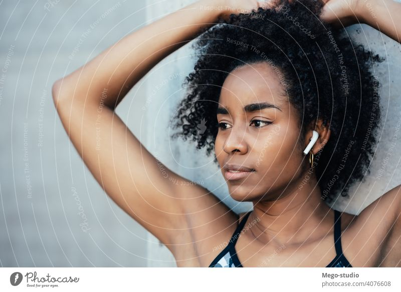 Afro athletic woman standing outdoors. fitness athlete sport exercise resting break ear pods enjoying relaxation leisure city sporty earbuds sportswoman active