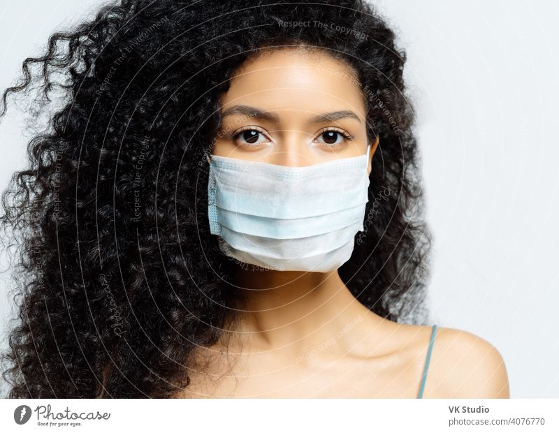 Serious Afro American woman tries to stop virus and epidemic disease, stays at home during infectious outbreak, wears medical mask, isolated on white background, being hospitalized, diagnosed