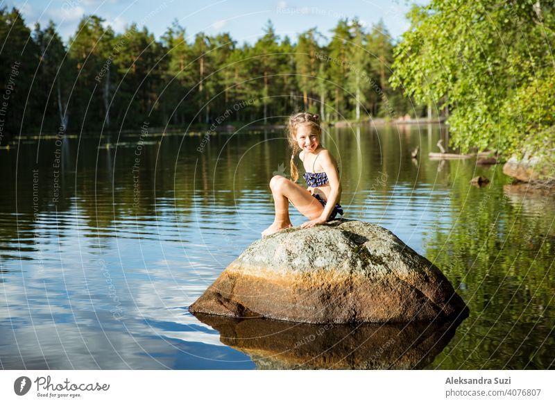 Cute little girl sitting on a rock in lake. Enjoying summer vacation. Child and Nature. Happy isolation concept. Exploring Finland. Scandinavian landscape.