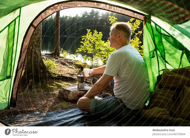 Man making coffee using espresso maker on campfire in forest on shore of a lake, sitting in tent, making a fire, grilling. Happy isolation concept. Exploring Finland. Scandinavian landscape.