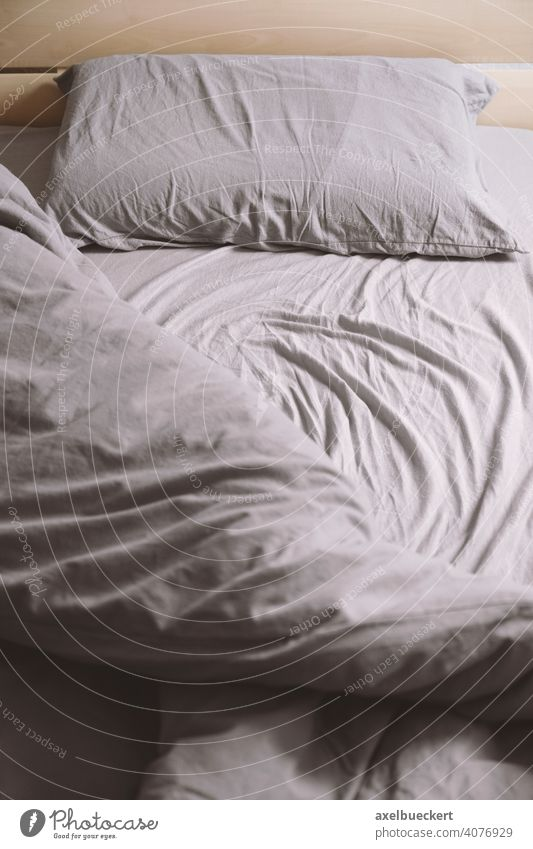 empty unmade bed with crumpled bedding or bedclothes single bed messy creased bedroom pillow morning sheet sleep indoor furniture duvet linen home interior