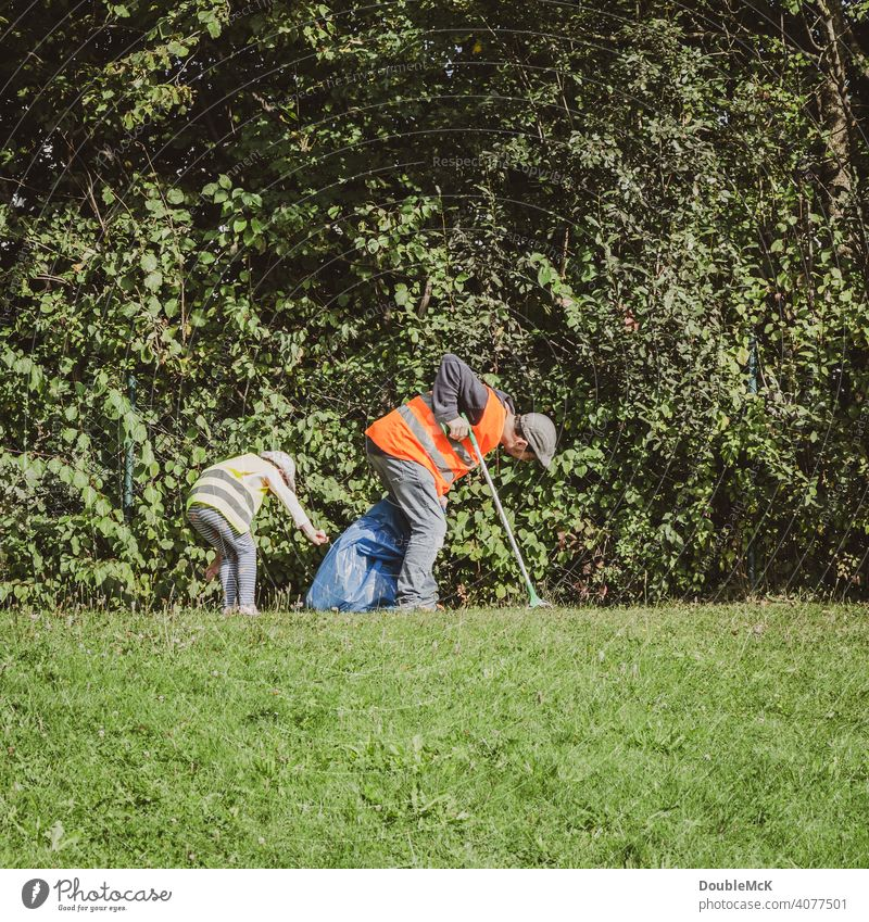 A man and a child search for trash in the bushes on World Cleanup Day clean up Action day social action Environment Trash September civic movement Eliminate