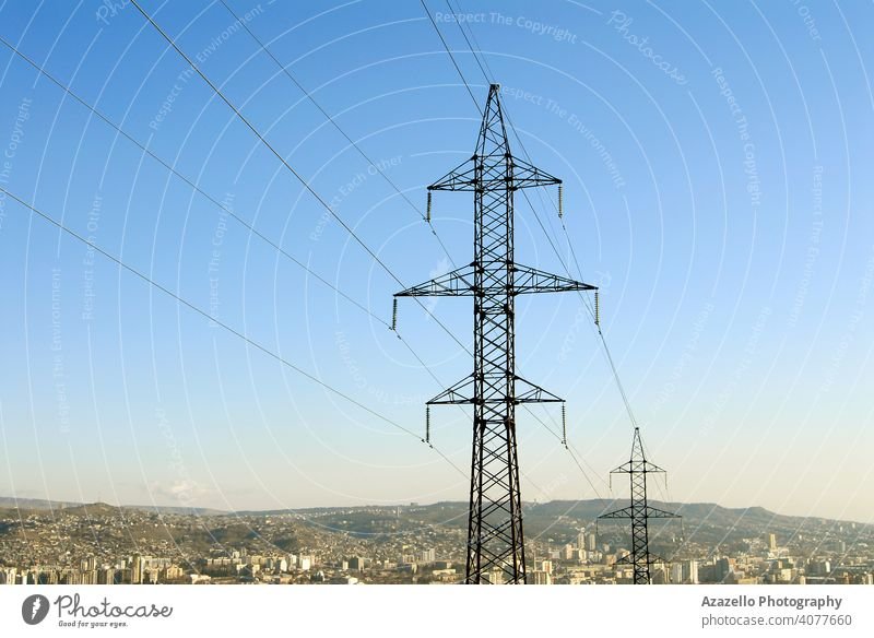 Electricity pylons with a cityscape. blue business cable civilization current danger design distribution ecology electric electrical electricity energy