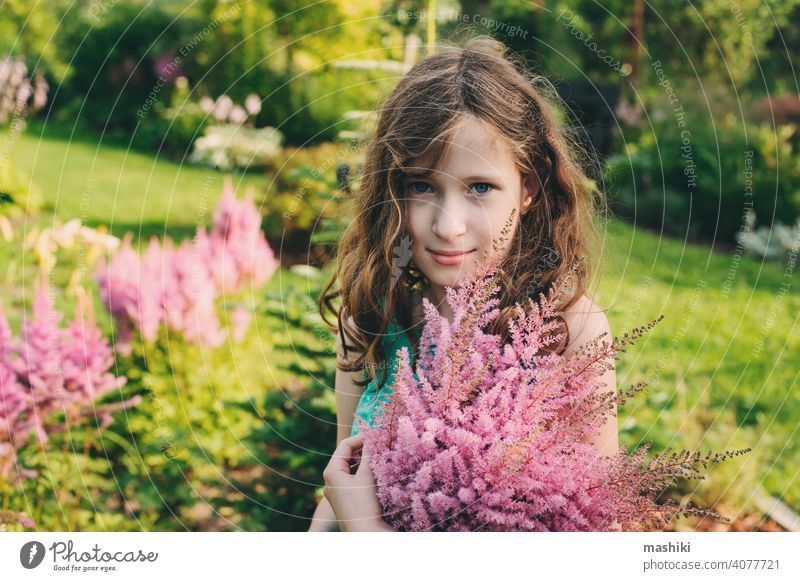 happy kid girl picking bouquet of astilbe flowers in summer garden child nature childhood outdoor happiness green cute fun little playing smiling young portrait