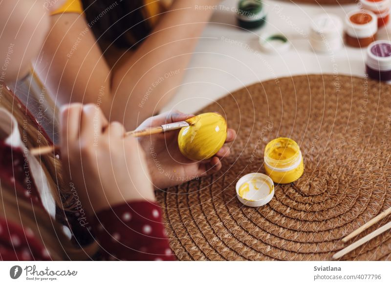 Little blonde at home in the kitchen paints Easter eggs in different colors for Easter easter spring child holiday preparation sisters brother bright family