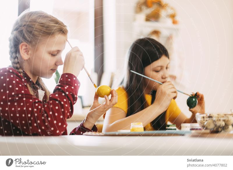 Two sisters are sitting at the table and painting Easter eggs in different colors for Easter, close-up easter spring child holiday preparation bright family