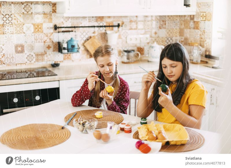 Two sisters are sitting at the table and painting Easter eggs in different colors for Easter easter spring child holiday preparation bright family girl white