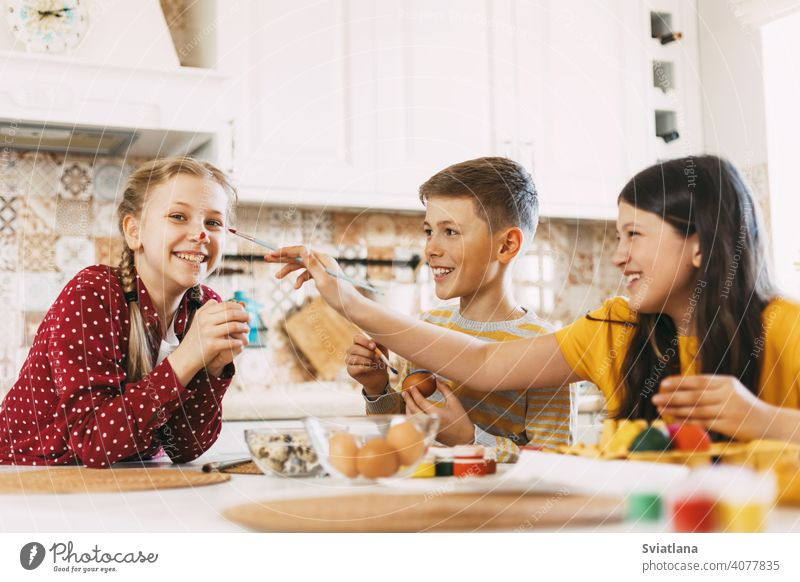 Two sisters and a brother are sitting at the table and painting Easter eggs in different colors for Easter, laughing and indulging easter spring child holiday