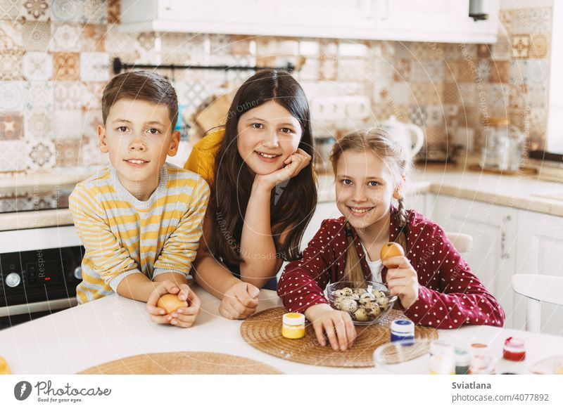Funny and cheerful children sitting at the table paint Easter eggs in different colors for Easter easter spring holiday preparation sisters brother bright