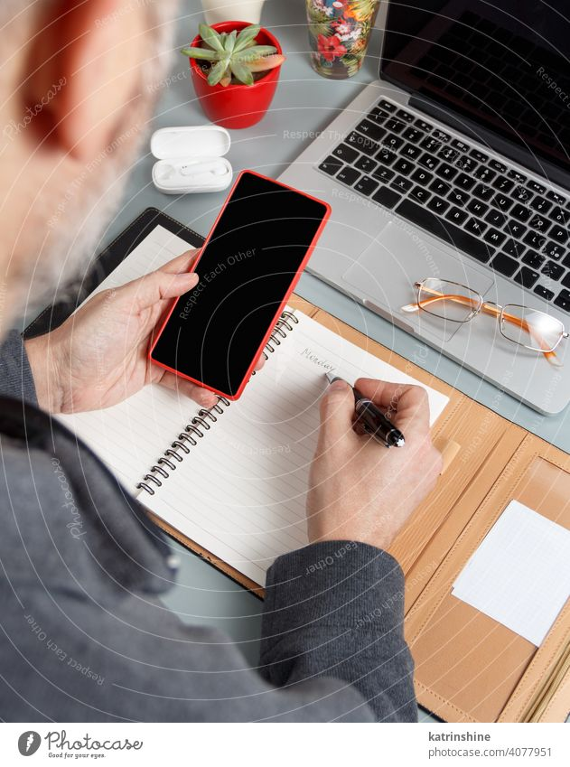 Man writing MONDAY in agenda and using cell phone on a grey office desk close up Business man hands write smart working laptop planner pen Caucasian faceless