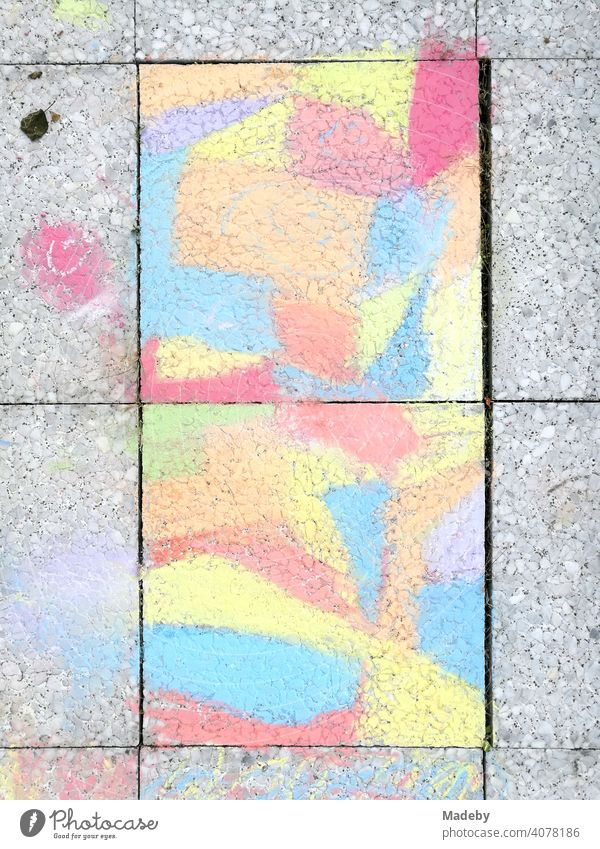 Grey paving stones painted with coloured chalk by a child on a balcony in Oerlinghausen near Bielefeld on the Hermannsweg in the Teutoburg Forest in East Westphalia-Lippe