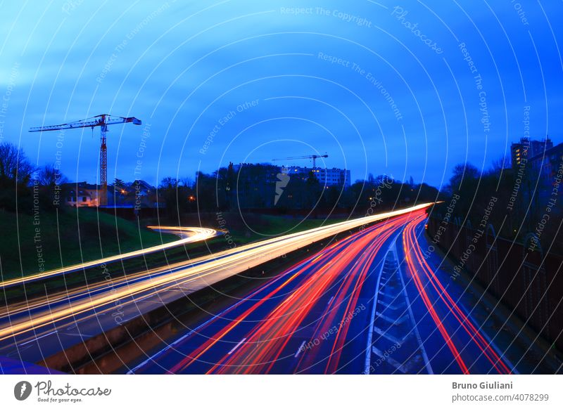 Light trail of cars on a highway during the morning. Spun vehicles on the road as seen from a bridge. Lightpainting scene. building city curve drive environment
