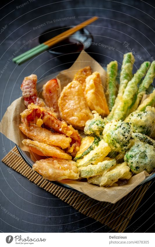 Side view of prepared Japanese vegetable tempura recipe with ginger ponzu sauce , black background with copy space appetizer bamboo bowl broccoli carrot