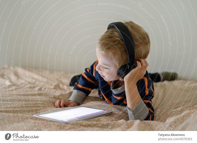 Boy using tablet on bed child boy internet technology learning modern home digital leisure education digital tablet communication childhood person indoor