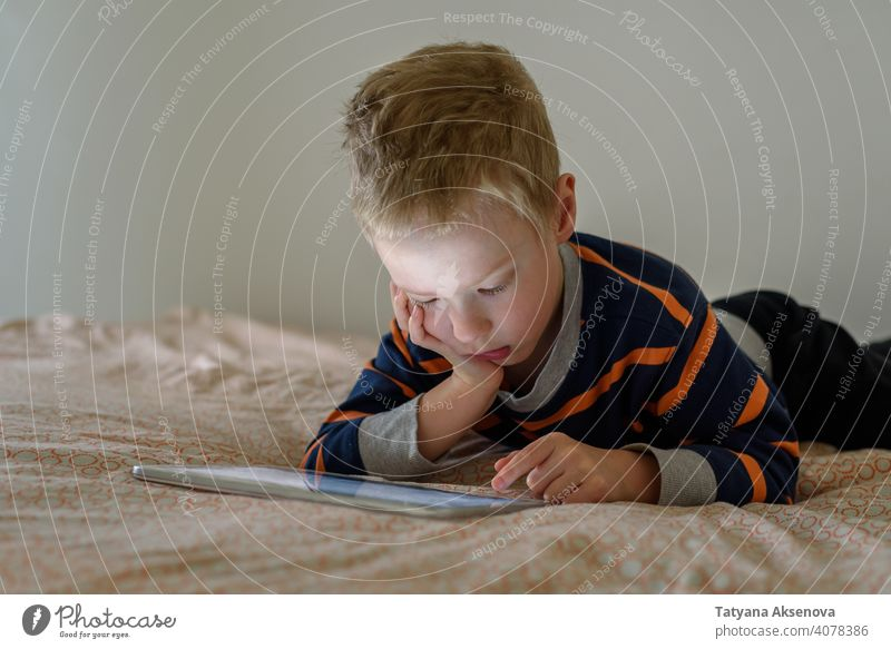 Boy using tablet on bed child boy internet technology learning modern home digital leisure education digital tablet communication childhood person indoor