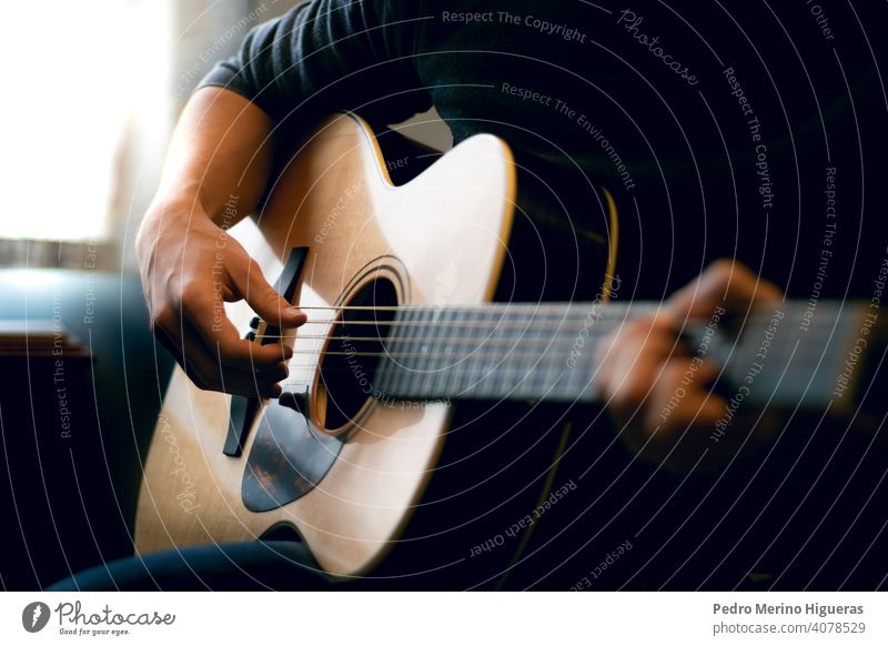 Young man playing acoustic guitar music musician room instrument male musical song young adult person people home guitarist lifestyle sound hobby leisure casual