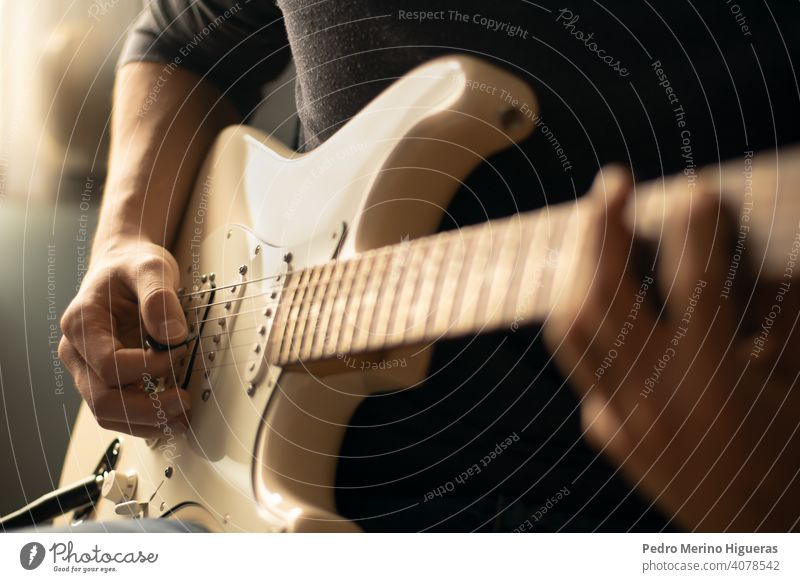 Man playing a white electric guitar. Close-up music home instrument male musician man guitarist adult musical young people lifestyle happy fun hobby person