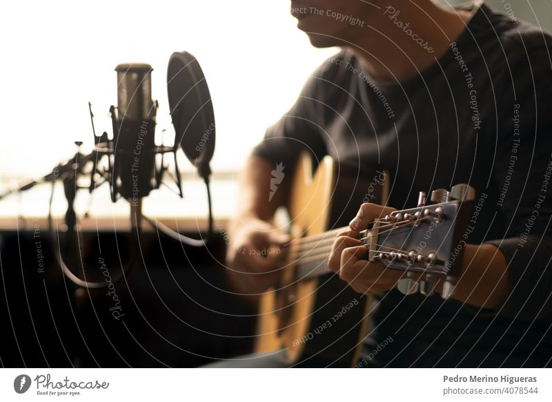 man playing spanish guitar and singing while recording it with a microphone musical instrument male person people human hat guitarist musician happy background
