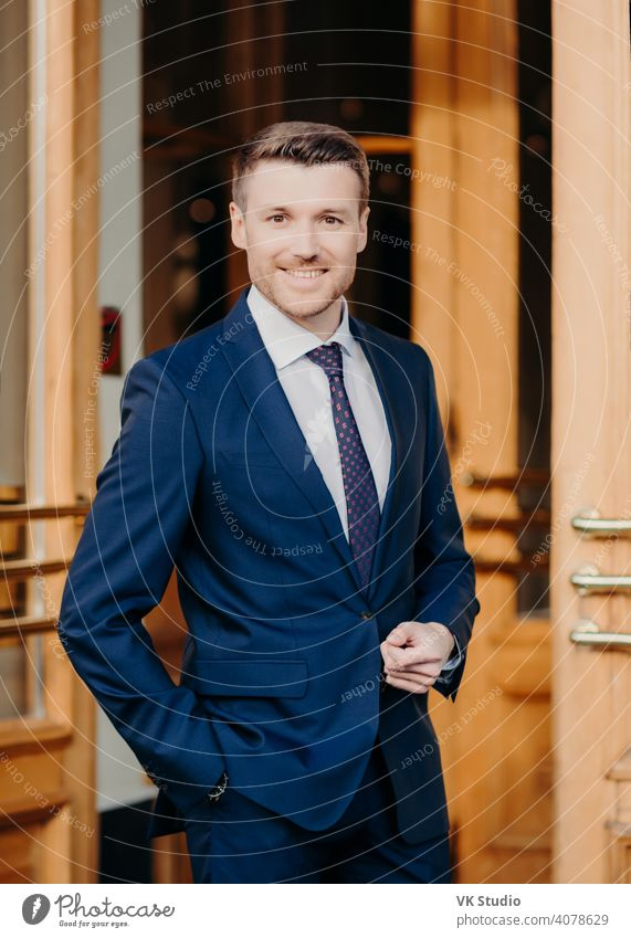 Attractive male executive manager in formal outft, keeps hand in pocket, has positive expression, stands near office, rejoices good achievement, confident in success. Male lawyer stands near doors