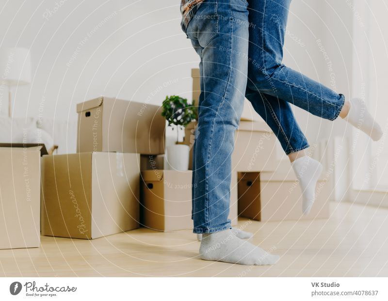 Faceless young couple move in new home, man lifts woman, have fun, surrounded with unpacked cardboard boxes, start new life in recently bought abode. Family, relocation and moving day concept