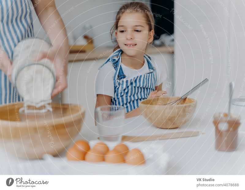 Curious little girl looks how mom prepares dough for pastry, learns to cook, gets culinary experience, wears apron. Faceless woman adds flour in bowl with other ingredients, pose in kitchen with child