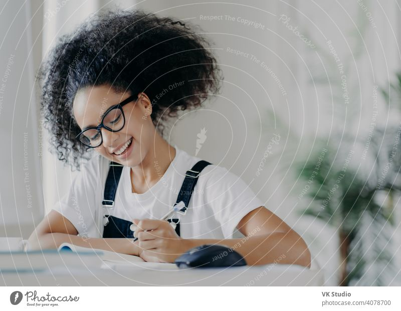 Happy Afro American female student writes down information, prepares for exams, sits in coworking space, has curly dark hair, wears optical glasses white t shirt and overalls, studies in spacious room