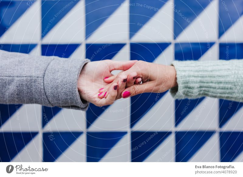 close up of two women holding hands against blue and white tiles. friendship or lgtbi concept lesbian love Porto right person symbol adult homosexual romantic