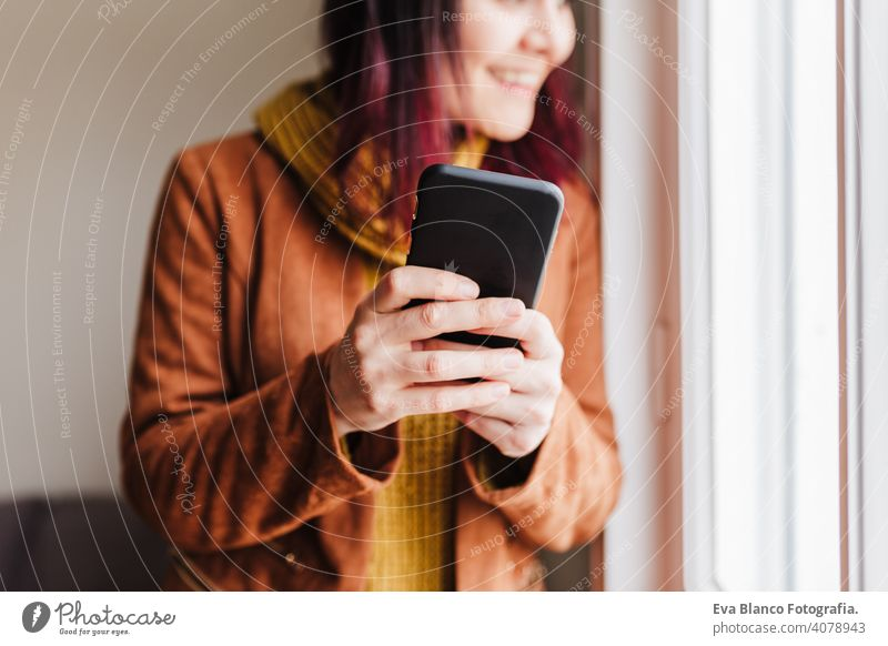 young beautiful woman at home using mobile phone by the window. Technology and lifestyle technology home office caucasian casual clothing smart phone brown