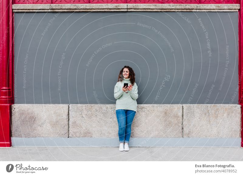 young caucasian woman using mobile phone outdoors in the city. Technology and lifestyle urban technology texting street cyberspace smart app text message happy