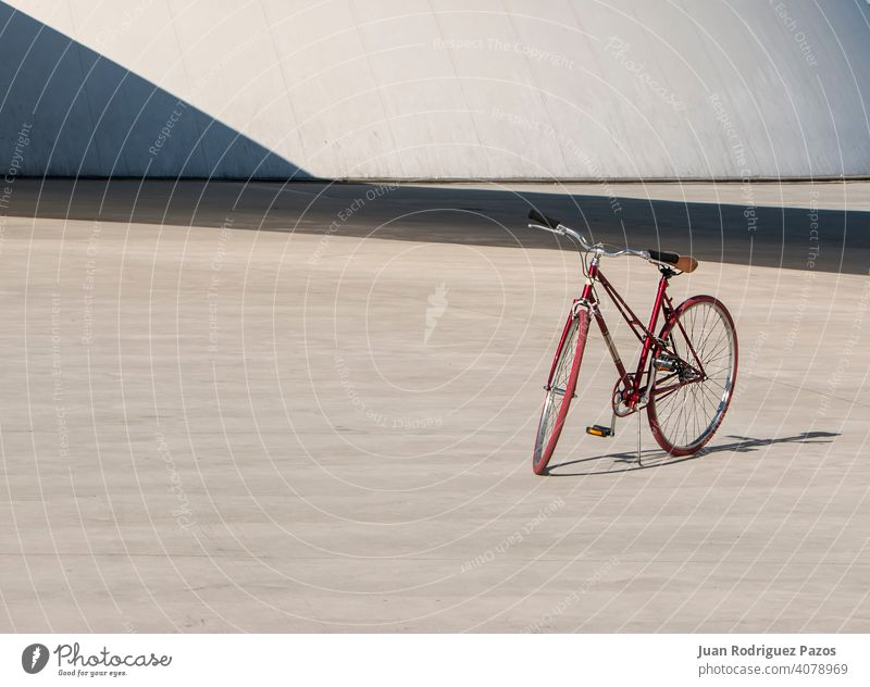 Red bike alone in concrete park travel bicycle outdoor sport background lonely transport wheel standing lifestyle nobody leisure city biking day red urban