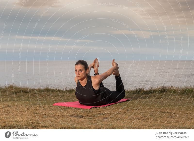 Woman in black sportswear exercising outdoors with the sea in the background. pilates yoga exercise healthy lifestyle woman mat stretching female fitness