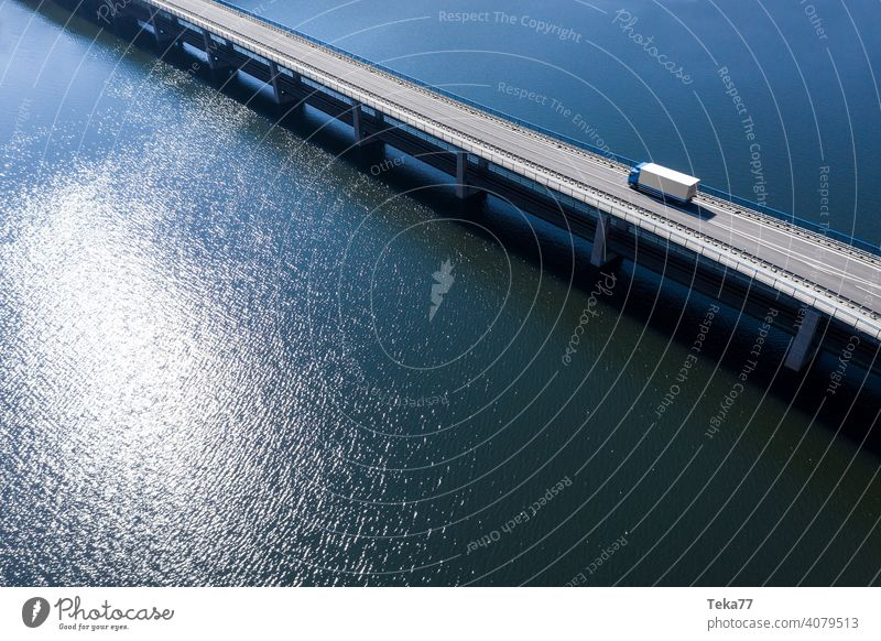 a truck driving on a bridge in the water truck drving future future tansportation sea lake bridge in water from above sun modern transportationmodenr truck