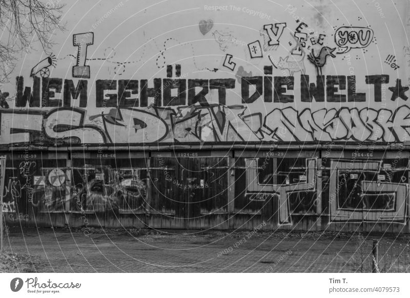 """a graffiti on the facade above the garages """"Who owns the world"""". Graffiti Lake Weißensee Berlin Garage door old Deserted Exterior shot Wall (building)"""