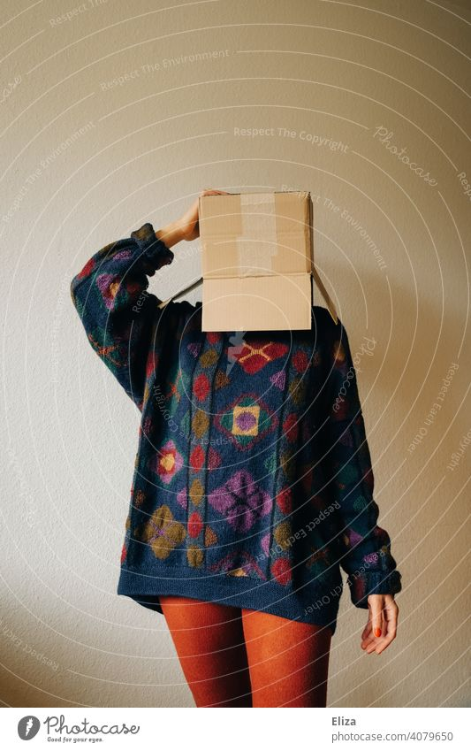 Woman in colorful clothes with a cardboard box on her head Cardboard Crate mail Order Anonymous Hide Exasperated Package variegated Carton Packaging Sweater