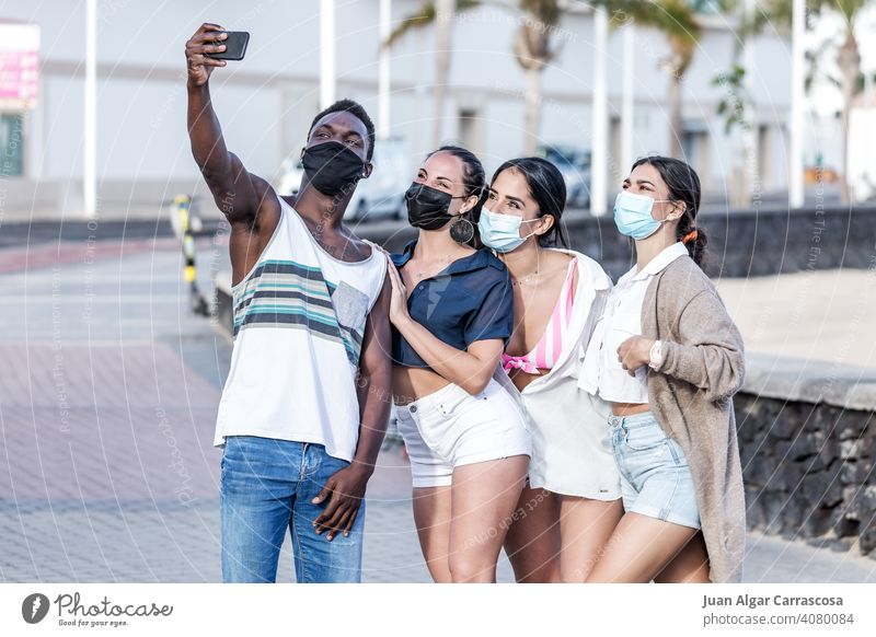 Company of diverse friends in masks taking selfie on street together company friendship city self portrait having fun protect multiethnic multiracial black