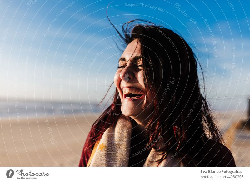 happy woman having fun at the beach on a windy day at sunset. Holidays and fun concept laughing happiness relax caucasian vacation holidays runway passage