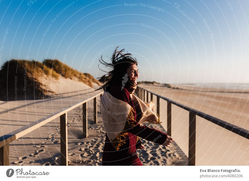 happy woman having fun at the beach on a windy day at sunset. Holidays and fun concept running laughing happiness relax caucasian vacation holidays runway