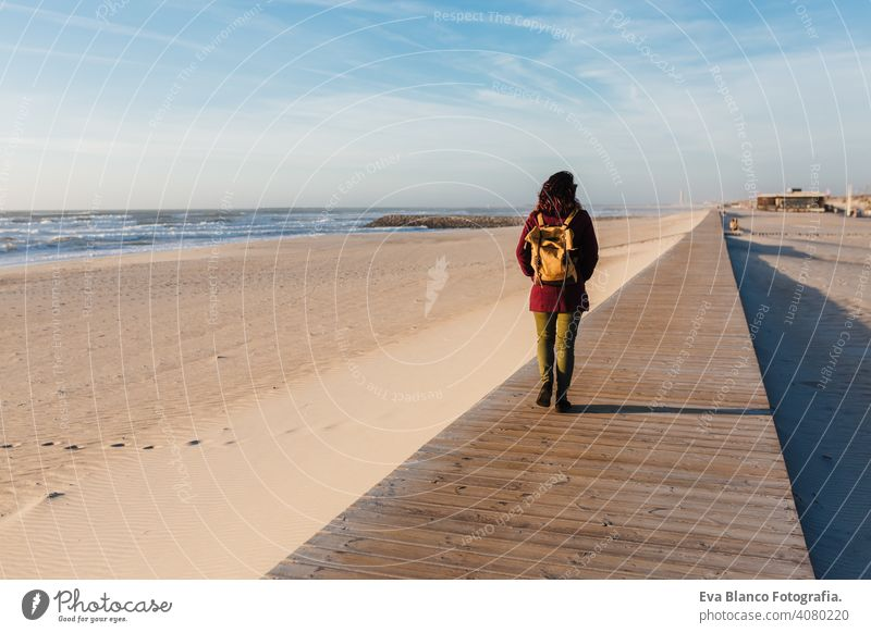 backpacker young caucasian woman relaxing at the beach at sunset. walking by wooden passage or runway. Holidays and relaxation concept vacation holidays