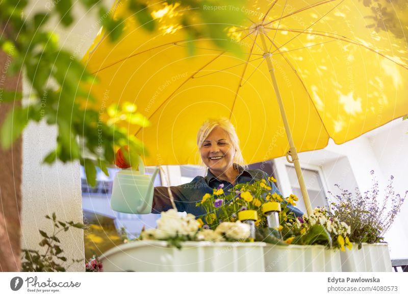 Senior woman taking care of her plants on the balcony smiling happy enjoying positivity vitality confidence people senior mature casual female Caucasian elderly